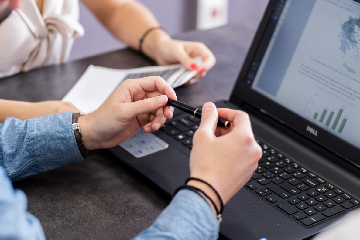 A pair of hands over a laptop keyboard holding a pen